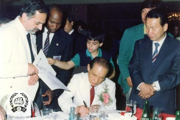 The Founder signs an autograph for John Polychroniou (20681) and Park Sang Tcheon (48) standing at the far right.