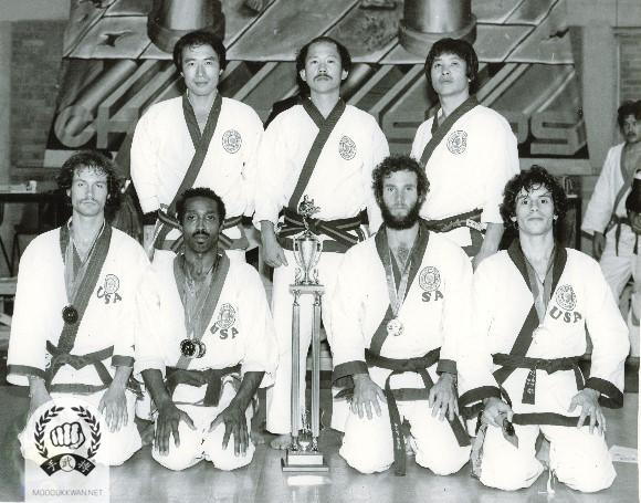 USA Team with officials; Seated from left: Brent Laymond (), Llyod Francis (), Doug Pratt (), and Gary Cholakian (). Standing from left: YK Hong (9193), HC Hwang (509), and CS Kim (2457). Team member Gary Tarr (20576) is not in the photo due to medical check up.