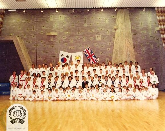 1985 Chil Song Hyung and Moo Pal Dan Khum clinic by the founder in England. The founder, Kang Uk Lee (70), HC Hwang (509), Louis Loke (23436), Peter Chin (19982) ar showing in this photo along with students of Moo Duk Kwan in England.