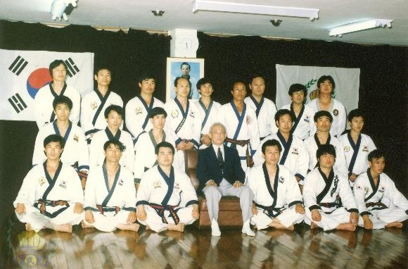 Clinic with Founder at MDK Headquarters in Korea. Standing left to right; Chun Kwan Ho, Kim Jong Hwan (18051), Oh Moon Seop (20943), Han Chi Seop (17453), Choi Ki Un (22360). Kneeling left to right; Kim Jin Oh, Kim Yu Eup (24015). Seated on floor; Hwang Dal Ho (22225).