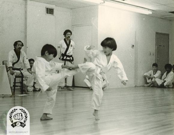 Children's free sparring at the Gup Shim Sa in 1976, Frank Bonsignore (15805) and H.C. Hwang (509) are seen in the background.